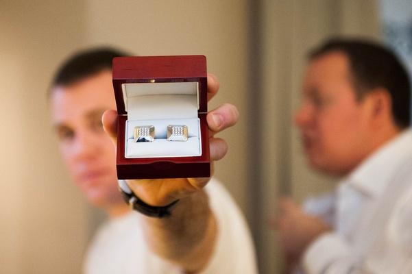 Groom holding box filled with custom diamond cuff links