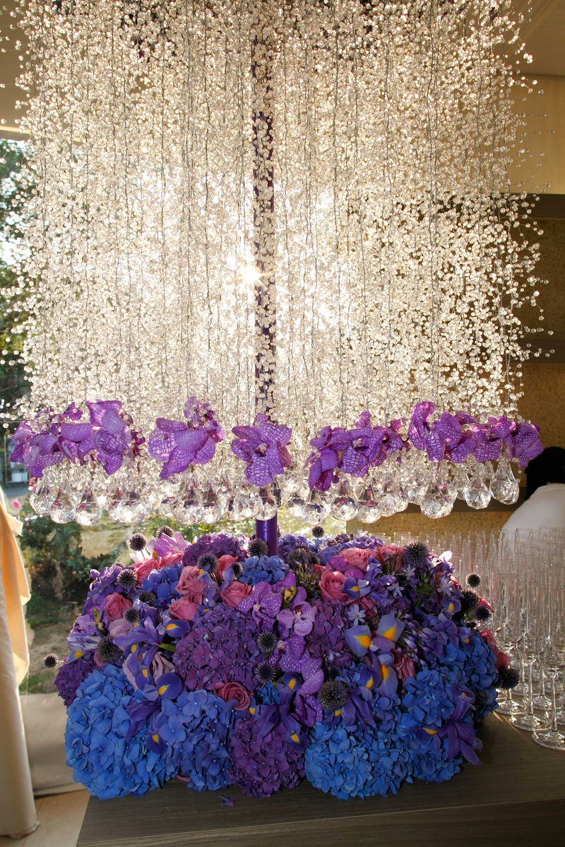 Whimsical garden themed wedding concept in shades of purple amp tall floral arrangement featuring blue pink and purple flowers and hanging white flowers crystals mightylinksfo