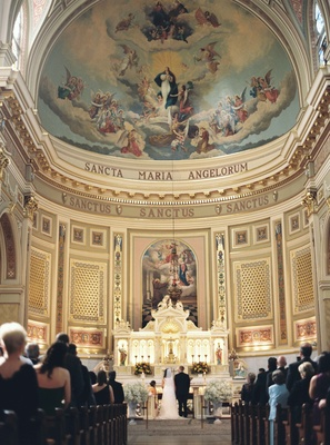 Bride and groom kneel at altar for St. Mary of the Angels Catholic Church in Chicago