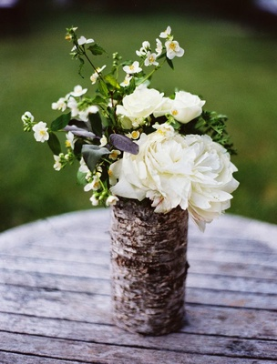 Outdoor wedding decor of vase wrapped in birch wood filled with white flowers and greenery
