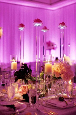 Purple and pink lighting on wedding reception table with crystal stands