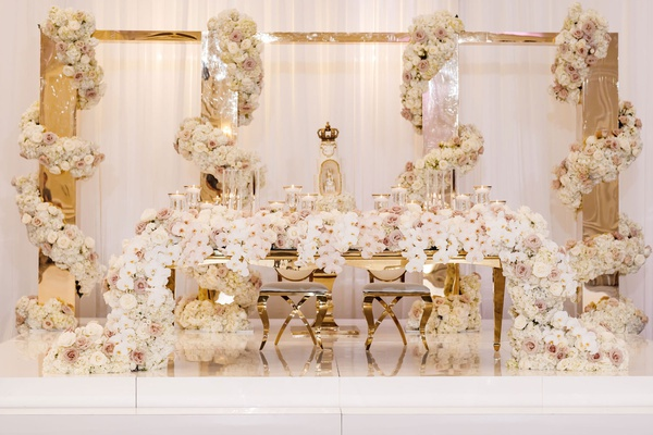wedding reception gold white decor sweetheart table on stage with castle and flower garlands gold