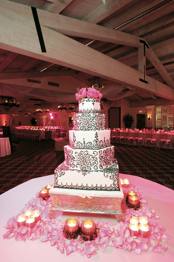 White cake with chocolate scroll work and pink flower topper