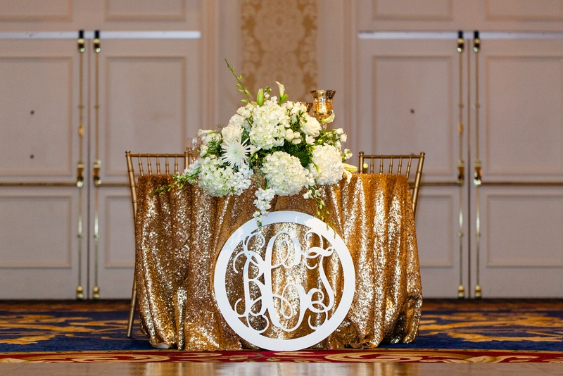 Gold sequin tablecloth on sweetheart table with white monogram cut out