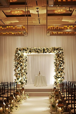 White flower and greenery chuppah at indoor ceremony