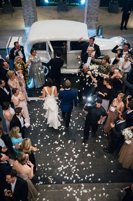 Bride and groom walking toward classic white getaway car through pathway of guests flower petals