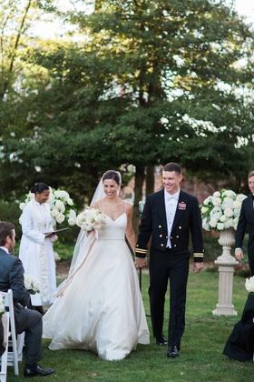 Bride in v-neck amsale wedding dress holding military groom navy uniform hand outdoor wedding