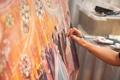 Artist painting scene of wedding reception on canvas