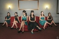 Teal and black bridesmaid dresses on red couches