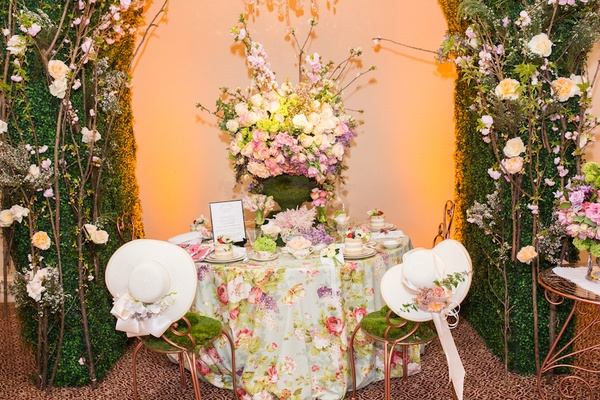 Bistro chairs with moss and white hats with fresh flowers
