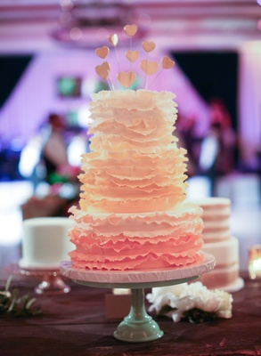 Three-layer wedding cake with ruffles and heart toppers