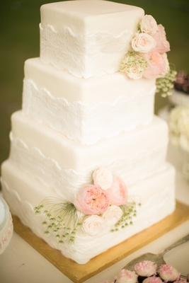 White wedding cake with lace details and pink roses