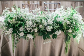 sweetheart table with lots of greenery with white flowers