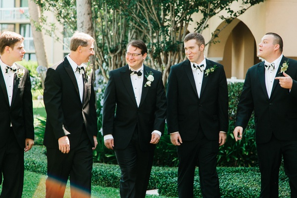Groomsmen in black suite and black-and-white bow ties with greenery boutonnieres