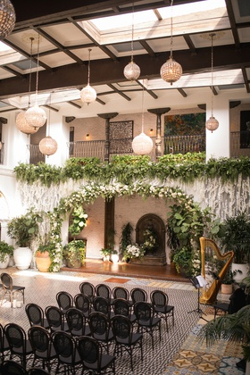 ebell long beach wedding ceremony with orchids and greenery from balcony, globe lights, black chair