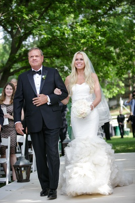 Bride in a fit-and-flare Vera Wang dress, sparkling sash, ruffled skirt, veil & father in black tux