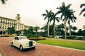 vintage white car driving in front of the breakers resort