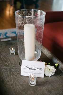 "Candle in votive with ""If you Instagram"" and wedding hashtag next to small candles"