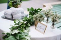 Grey yarmulke table with wedding hashtag sign, baby's breath, green garland on table