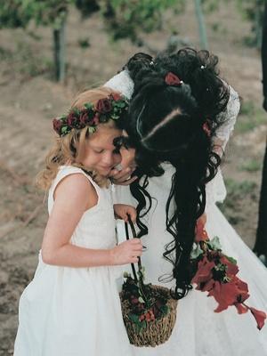 Flower girl in white dress holding basket