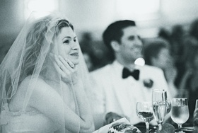 Black and white image of bride in veil at reception