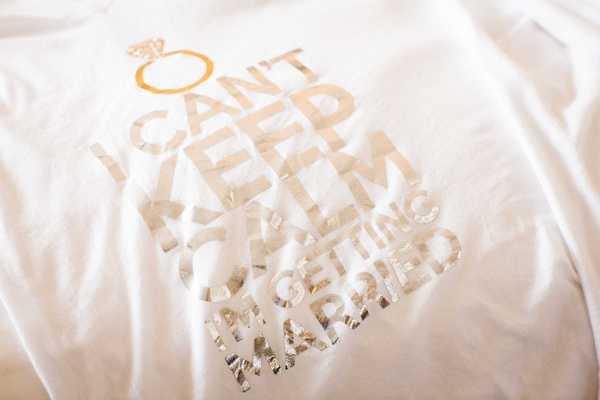 White T-shirt with metallic silver lettering reading I can't keep calm I'm getting married with ring