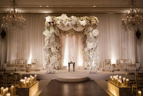 wedding furniture gold on both sides of chuppah with white flower accents candlelight lit up boxes