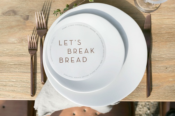 wedding reception modern menu circle with let's break bread in the middle copper flatware