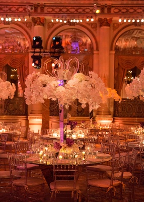 Clear chiavari chairs around mirror top round table with orchid centerpiece lucite mirror details