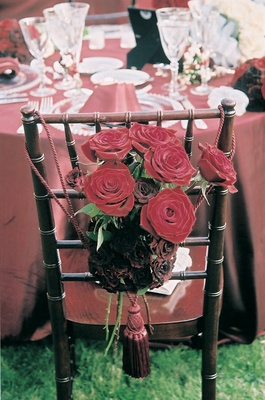 cluster of red roses attached to back of chair