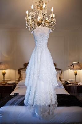 Monique Lhuillier tiered skirt wedding dress hanging from chandelier
