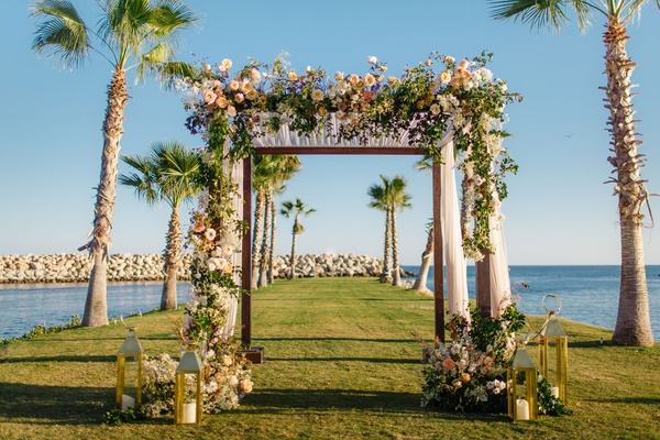 destination wedding in cabo san lucas, chuppah with peach flowers, gold lanterns