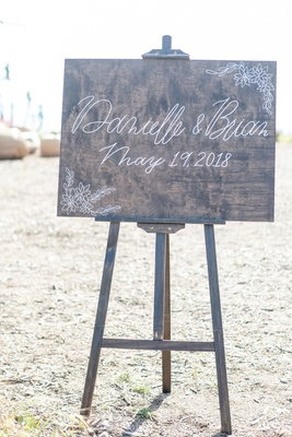 wedding ceremony outdoor wood sign with modern calligraphy in white names and wedding date easel