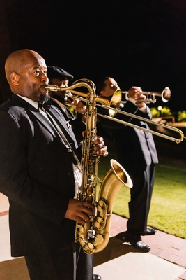 Men playing saxophone, trombone, and trumpet at wedding reception outside