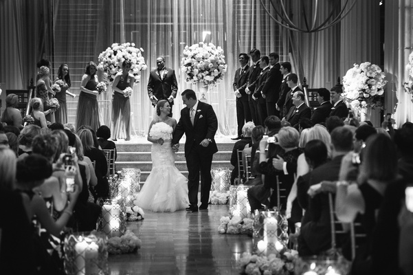 Black and white photo of couple walking up aisle