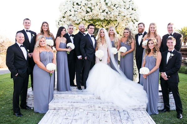 Bride in galia lahav mermaid wedding dress with groom in tuxedo bridesmaids in periwinkle grey