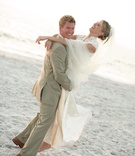 Groom in khaki suit picks up bride in lace wedding dress on beach