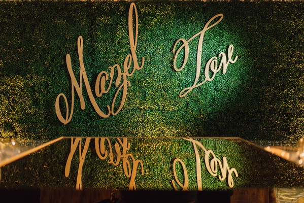 Wedding signage mazel tov modern calligraphy gold on green hedge wall mirror floor