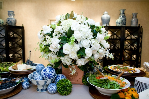 White flower arrangement with fruit and cheese plates