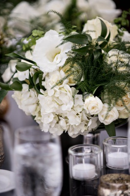 white hydrangeas, ivory roses, greenery, low wedding centerpiece with white florals and greenery