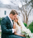 Bride in Berta wedding dress cascading white greenery bouquet groom in suit with bow tie cuddle