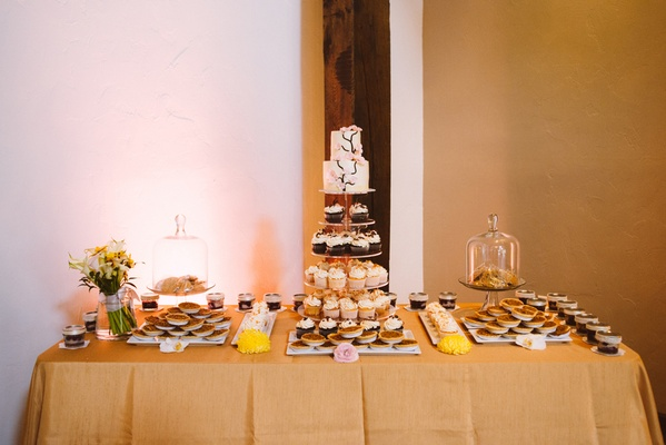 Neutral tablecloth topped with cupcakes and cookies