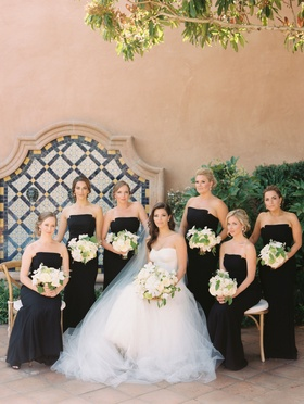 Bridesmaids in black dresses by jill stuart strapless necklines bride in white neutral bouquets