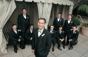 Groomsmen outside in black tuxedos with bow ties