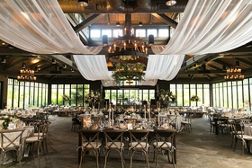 wedding reception in barn drapery rafters beams chandelier greenery wood table chairs