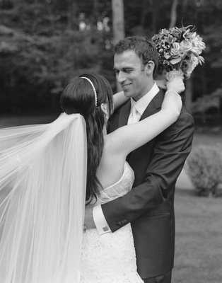 Black and white photo of bride with veil and groom