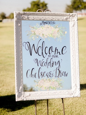 White antique frame with mirror welcome sign flower design and calligraphy welcome to our wedding