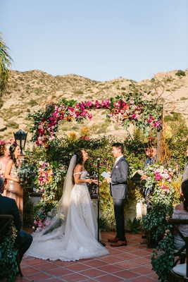 wedding ceremony mountain view light pink pink yellow orange flowers sunny vow exchange ranch venue
