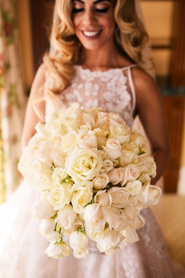 bride holding bouquet of white cream rose flowers semi cascading design high neck bridal gown