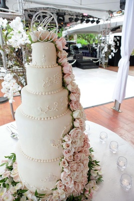 White wedding cake with light pink and white roses topped with couple's monogram